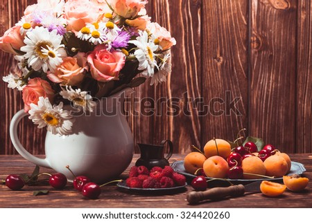 Summer still life with peaches, raspberries, cherries and flowers on a wooden table - stock photo
