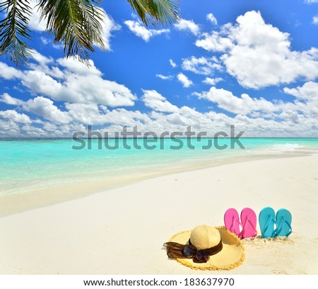 Summer straw hat with sunglasses and flip flops on the tropical beach  - stock photo