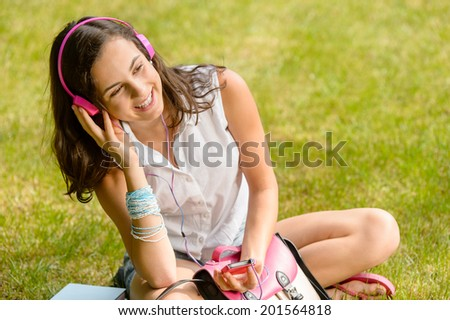 Summer student girl listening to music sitting on grass smiling - stock photo