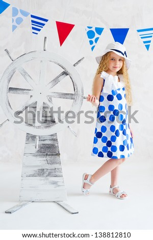 Summer style girl in fashion dress next to decorative wooden steer wheel - stock photo
