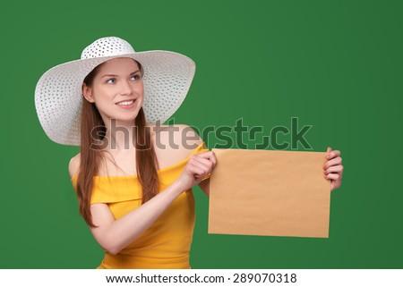 Summer style woman showing blank parcel - big envelope with copy space for text looking away, over green background - stock photo