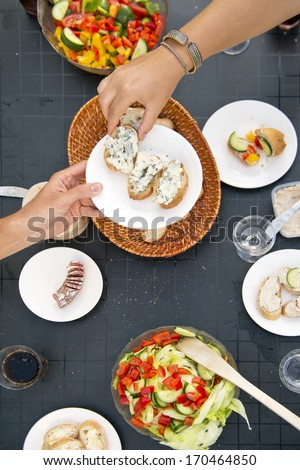 Summer Styled dinner table, with one hand passing a plate with bread and French Blue Cheese to another dinner guest, seen from above - stock photo