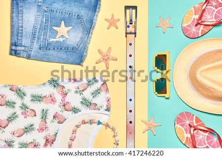 Summer. Summer background. Summer girl clothes set, accessories. Summer fashion T-shirt, stylish hat, necklace and trendy hipster sunglasses. Unusual modern. Summer Overhead, top view on yellow blue - stock photo