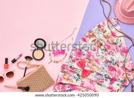 Summer.Summer fashion.Girl clothes accessories set.Woman essentials. Cosmetics, makeup.Stylish handbag clutch, dress, hat, necklace, sunglasses .Unusual overhead summer outfit, summer top view on pink - stock photo