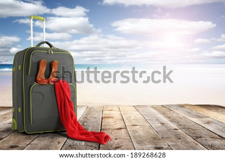 summer sun and suitcase with red decoration of towel