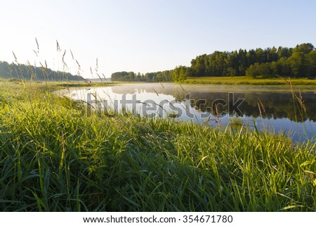 Summer sun Morning on the river bank in the village. bright colourful fine sunrise outdoors. - stock photo