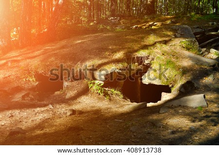 Summer sunny landscape - entrance to megalith on the territory of Vera Island in Southern Urals, Russia. It is the part of greatest megalithic complex of the Ural Mountains. Soft focus processing - stock photo