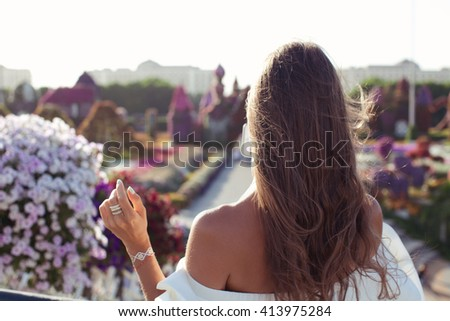 Summer sunny lifestyle fashion lady taking travel picture with phone in flowers park. Unrecognizable female young adult enjoying summer vacations in sexy white dress. (focus on shoulder) - stock photo