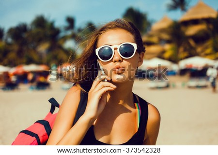 Summer sunny lifestyle fashion portrait of young stylish hipster woman walking on beach,wearing cute trendy outfit,talking on phone,travel calls,hikes,smiling enjoy her weekends,smartphone,connect - stock photo