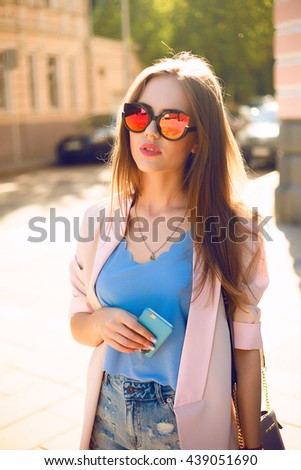 Summer sunny lifestyle fashion portrait of young stylish hipster woman walking on street,wearing cute trendy outfit,talking on phone ,smiling enjoy weekends,travel with backpack,coffee,rest,lounge - stock photo