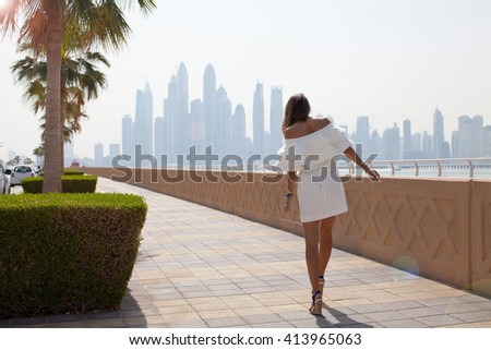 Summer sunny lifestyle fashion portrait of young stylish woman walking on Dubai street, wearing cute trendy outfit.