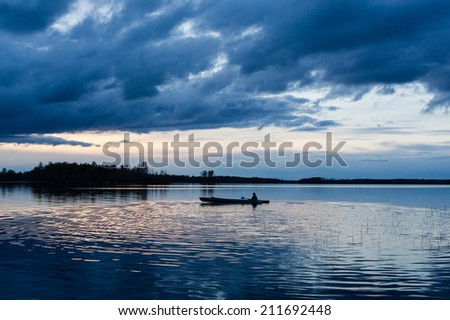 Summer sunset kayaking at Vuoksa lake - stock photo