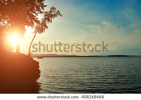 Summer sunset landscape - silhouettes of trees on the cliff against the picturesque sky and water of Irtyash Lake in Southern Urals, Russia  - stock photo