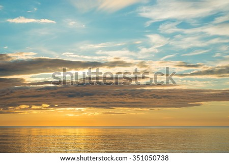 Summer sunset on the beach with dramatic clouds over the sky