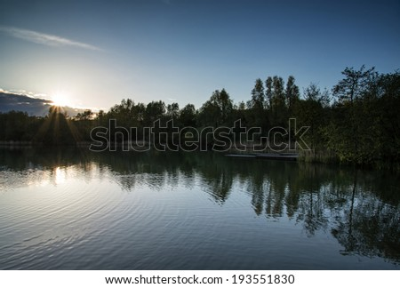 Summer sunset reflected in calm lake waters - stock photo