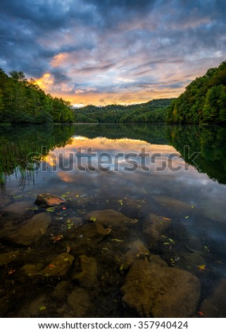 Summer sunset reflects on the surface of a clear mountain lake in the Appalachian Mountains - stock photo