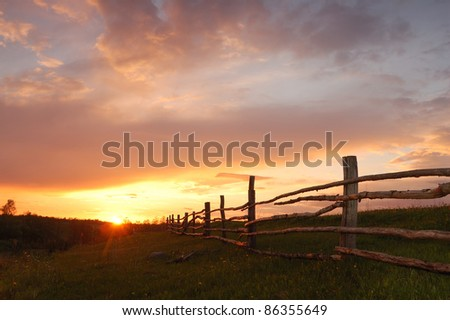 Summer sunset with a wooden fence - stock photo