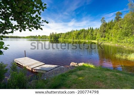 Summer Swedish lake in morning light - stock photo