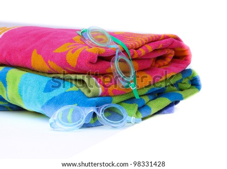 Summer Swim Goggles and brightly colored towels on isolated white background - stock photo