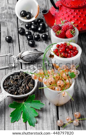 Summer tea with berries.Fruit tea with raspberries,currants in the red stylish kettle