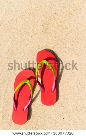 Summer theme with red flip flop on sandy beach