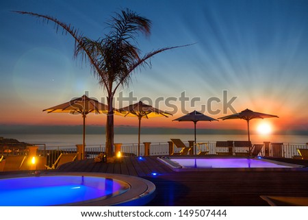 Summer time: beautiful dawn at pool area with palm and parasols, Tropea, Italy - stock photo