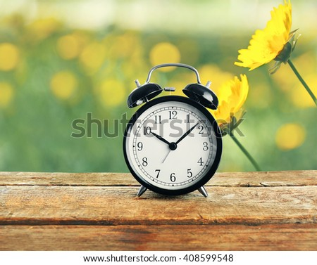 Summer time concept. Alarm clock on wooden table, cosmos flowers in the field background - stock photo