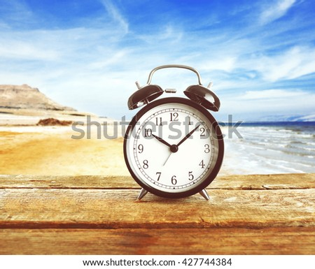 Summer time concept. Alarm clock on wooden table on beach background - stock photo