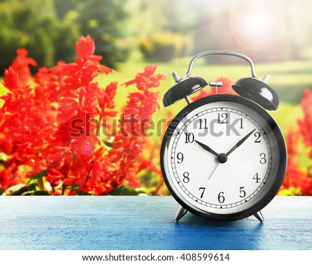 Summer time concept. Alarm clock on wooden table on  field background - stock photo