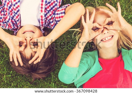 Summer time fun. Top view of two cute little children making faces and smiling while lying on the green grass together - stock photo