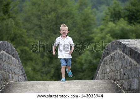 summer time : little blond boy running on a bridge - stock photo
