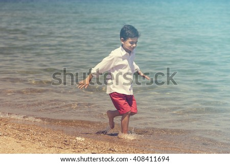 Summer time. Little boy having fun on the beach. Image with shallow depth of field cross processed for retro look