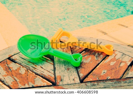 Summer toys on wooden table  at swimming pool. - stock photo