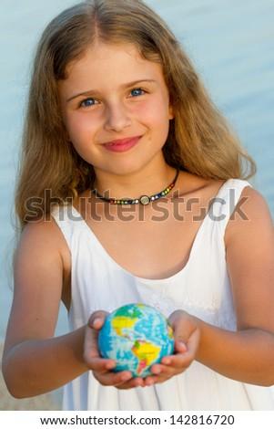 Summer travel concept - Globe on child hands - stock photo
