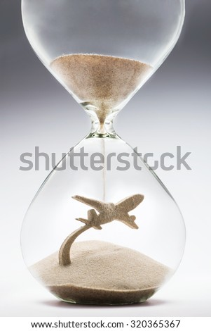 Summer travel. Hourglass falling sand taking the shape of a plane taking off