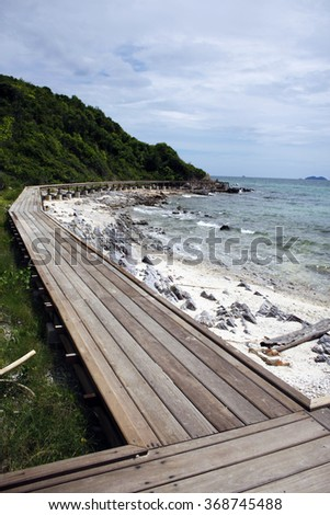 Summer travel vacation and holiday concept wooden long pier at coast against blue sky and water - stock photo