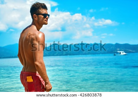 Summer Travel Vacation. Handsome Man With Sexy Body In Fashionable Sunglasses Sunbathing, Tanning At Sea Beach. Fitness Male Model With Sunscreen Lotion, Sun Block Skin Protection Cream In Pocket - stock photo
