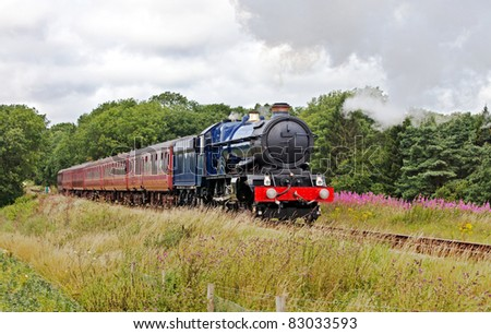 Summer trips in steam. Large blue steam train on a day trip with passengers through a summer scene - stock photo