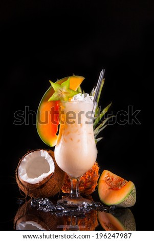 Summer tropical fresh drink on black glass, table with exotic fruits.