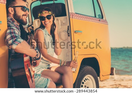 Summer tunes. Happy young couple enjoying time together while sitting in their retro minivan with sea in the background - stock photo