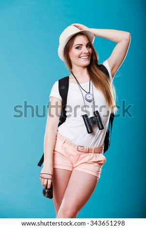 Summer vacation and tourism concept. Young woman in straw hat with backpack binocular compass on blue portrait