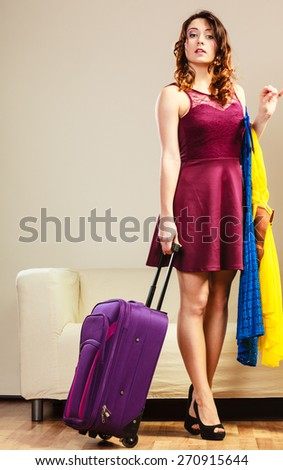 Summer vacation and travel concept. Woman preparing packing to trip, standing with clothes and bag suitcase at home