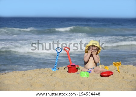 Summer vacation: Baby playing peekaoo on the beach - stock photo