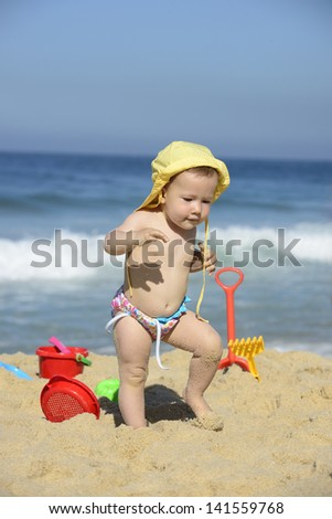 Summer vacation: Baby walking in the sand with beach toys - stock photo