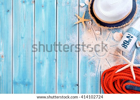 Summer vacation beach background theme with seashells, shape of sun in sand, red rope, sun tan bottle and hat with copy space over painted blue wood planks - stock photo