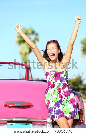 Summer vacation car road trip freedom concept. Happy woman cheering joyful during holiday travel in pink vintage car. Beautiful young mixed race Caucasian / Chinese Asian female model in Havana, Cuba