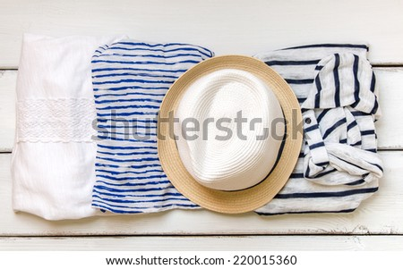 Summer vacation clothes and a hat in white and blue tones. - stock photo