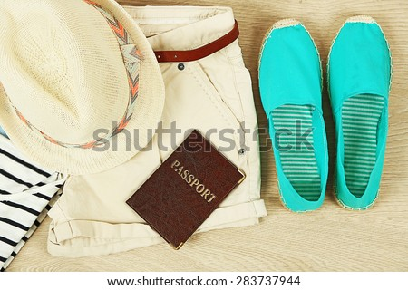 Summer vacation clothes, shoes and hat on wooden background - stock photo