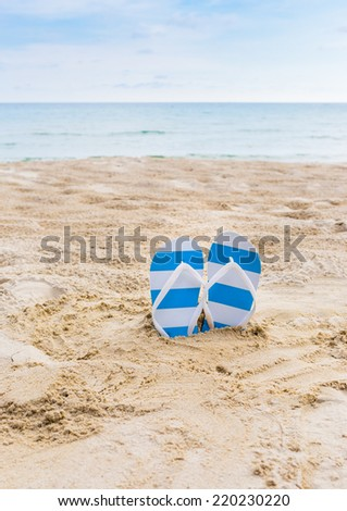 Summer vacation concept--blue Flipflops on a sandy ocean beach
