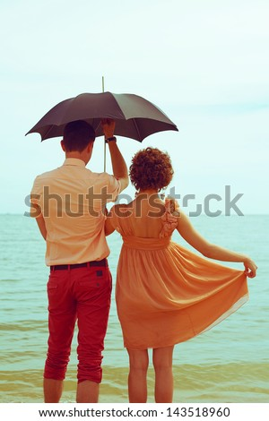 Summer vacation concept. Couple standing on beach near water and holding black umbrella. Hipster style. Copy-space. Outdoor shot